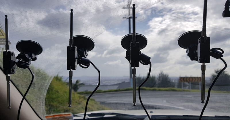 Low cost direction finding array mounted to vehicle windshield.